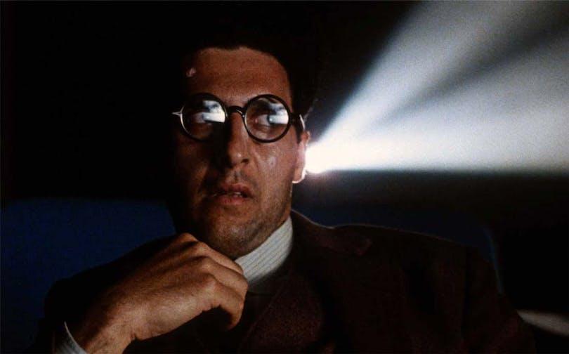 """John Turturro sitter framför en projektor i """"Barton Fink"""""""