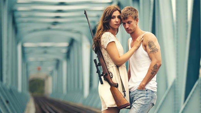 Paret i de odödliga står och håller om varandra. Kvinnan har ett gevär hängande på sin rygg.
