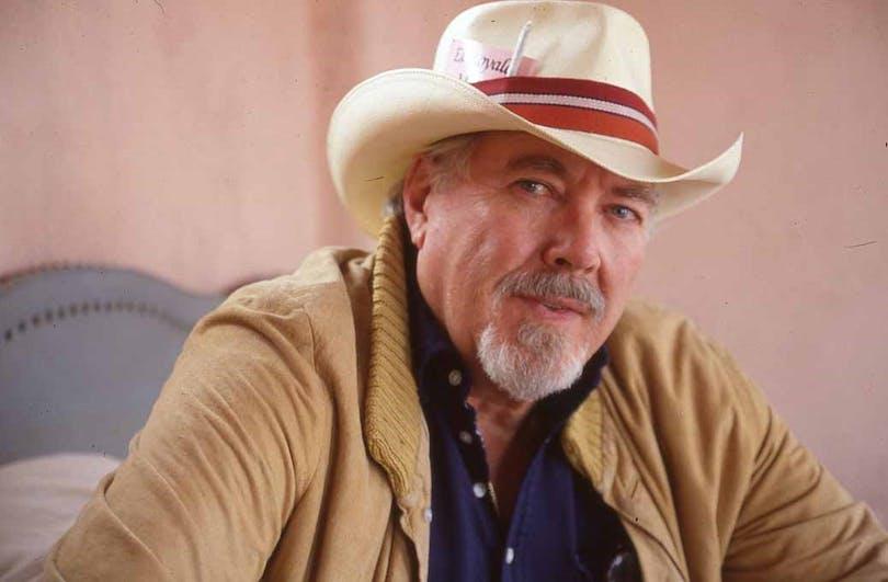 Robert Altman sitter med vit hatt mot en rosa bakgrund.