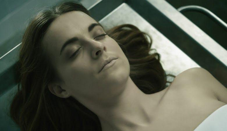 Anna Fritz ligger på en bår.