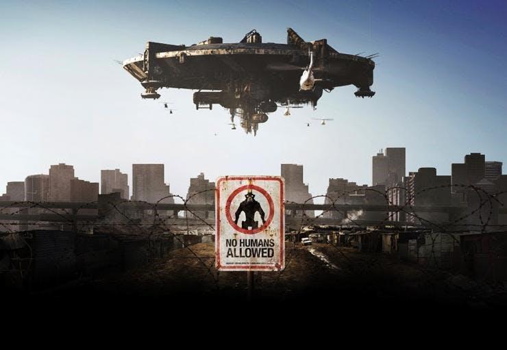 """En bild från Sci-fi filmen District 9. Ett rymdskepp syns på himlen över Johannesburg och en skylt där det står """"no humans allowed"""" är i fokus."""