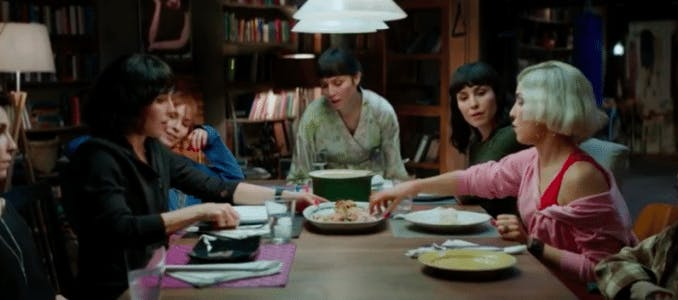 """Noomi Rapace som alla sju systrar runt matbordet i """"Seven Sisters"""""""