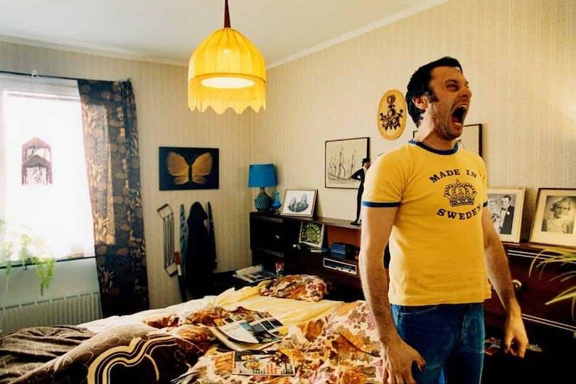 """Michael Nyqvist står i en lägenhet, iklädd en gul t-shirt, och skriker i """"Tillsammans""""."""
