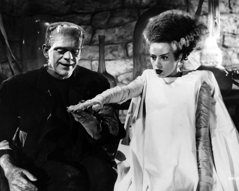 Ur Frankensteins brud. Monstret till vänster håller handen med den kvinnliga skapelsen som stirrar tomögt ut framåt.