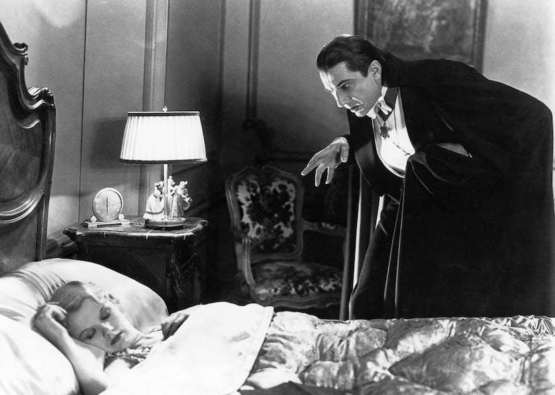 Bela Lugosi står som Dracula lutande över en kvinna som sover.