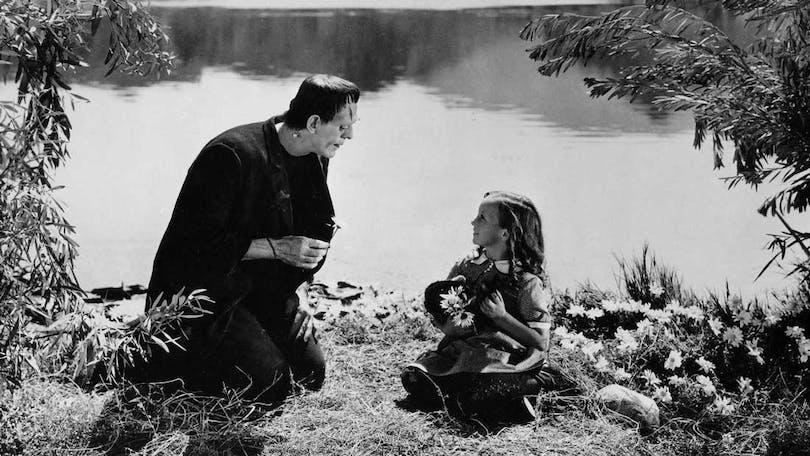 Ur Frankenstein. Monstret och en liten flicka sitter i gräset och plockar blommor vid en sjö.