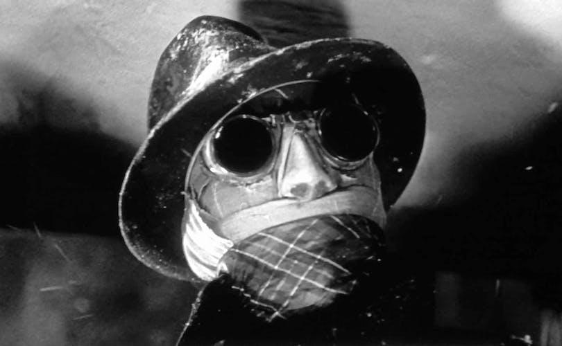 En närbild på Den osynlige mannen. Han har på sig sina svarta solglasögon och hatt. Hans ansikte är inlindat i bandage.