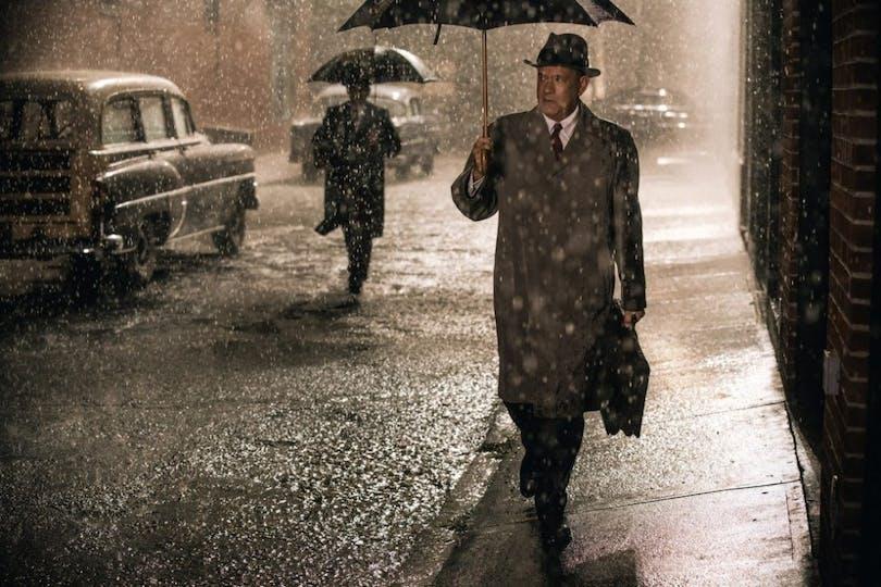 Tom Hanks går i regnet under ett paraply i Bridge of Spies.