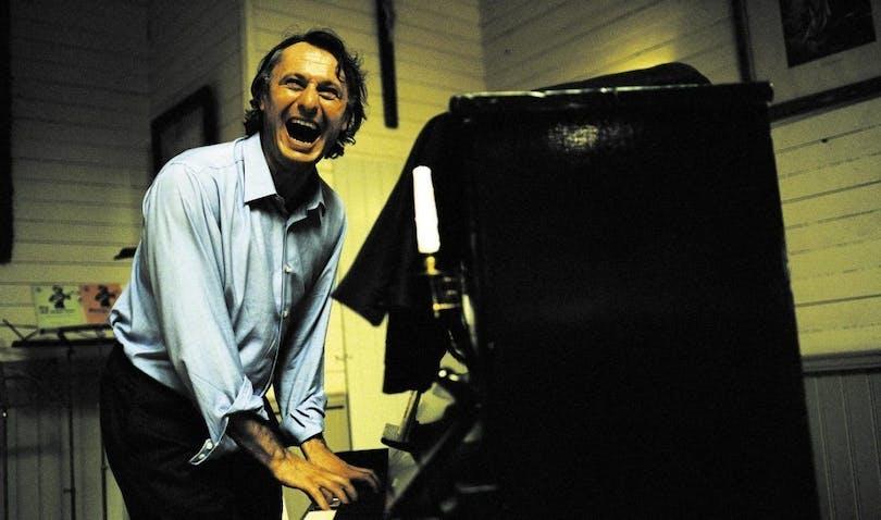 Michael Nyqvist i Så som i himmelen. Han spelar piano och skrattar högt.