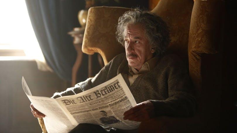 """Geoffrey Rush som Albert Einstein i """"Genius"""". Han sitter i en fåtölj och läser tidningen."""