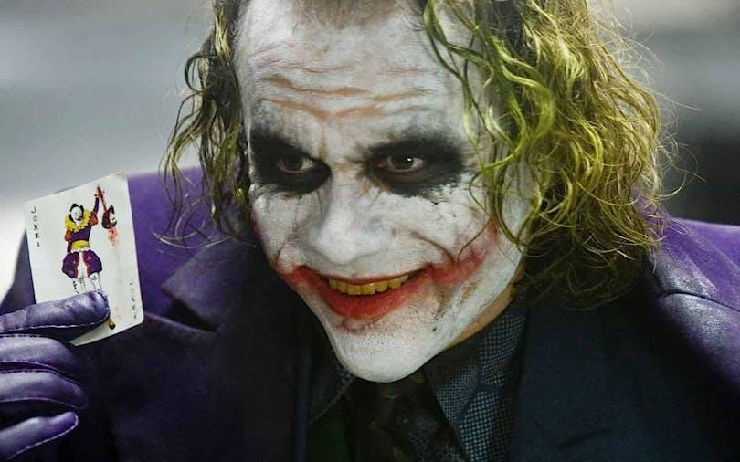 Heath Ledger som Jokern i The Dark Knight från 2008 där han håller kortet Jokern i handen.