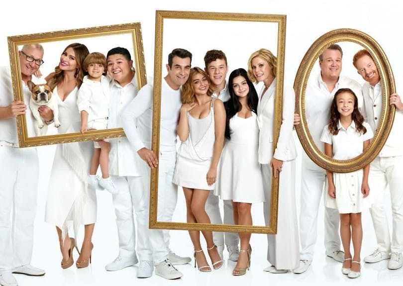 Poster med familjerna i Modern Family, alla klädda i vitt med ramar som visar vilken familj som de tillhör.