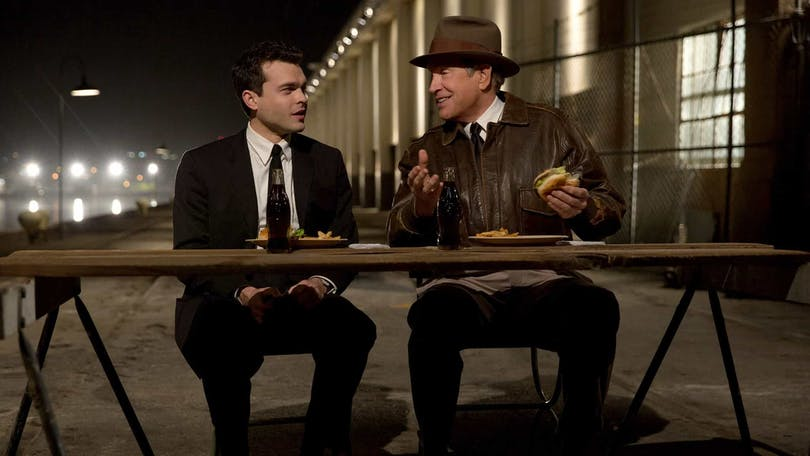 Frank (Alden Ehrenreich) och Howard Hughes (Warren Beatty) sitter på en pir vid ett bord och äter hamburgare i Rules Don't Apply.