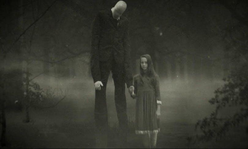 En svart-vit bild på Slenderman som står och håller en liten flicka i handen,