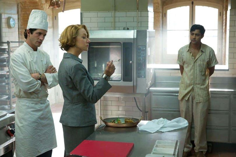 Från filmen 100 steg från Bombay till Paris. En kvinna står i ett kök och provsmakar mat medan två kockar ser på.