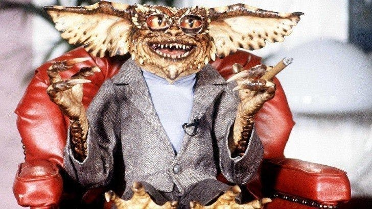 En Gremlin sittandes i kostym, cigarr och glasögon
