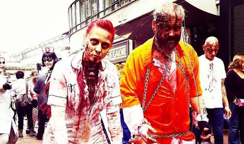 Två personen utklädda till zombies i London