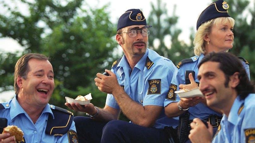 Från Kopps. Fyra poliser sitter tillsammans och äter lunch.