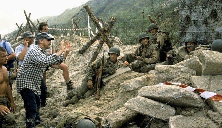 """Steven Spielberg förklarar något för resten av gruppen under inspelningen av Normandie-scenen i """"Rädda menige Ryan""""."""