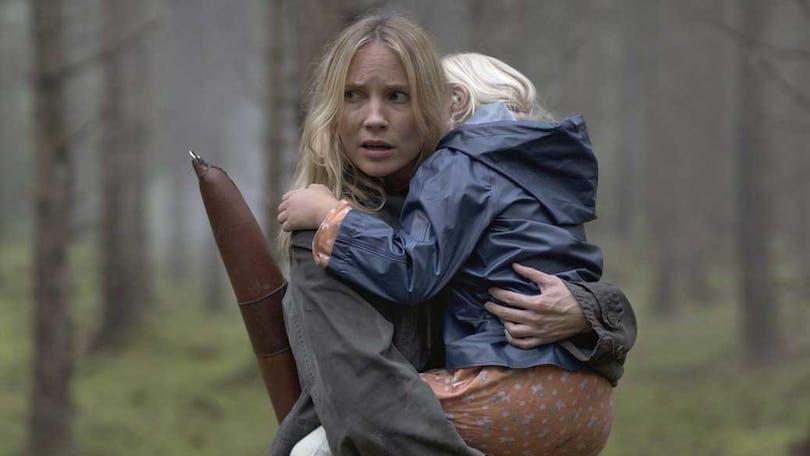En kvinna är ute i skogen och håller ett barn i famnen. Från Jordskott.