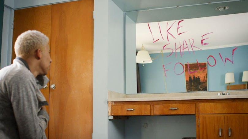 """Från filmen """"Like.Share.Follow"""". Garret tittar på en spegel där någon har skrivit Like.Share.Follow med röda bokstäver."""