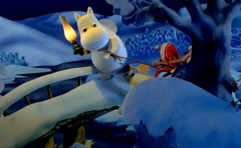 Mumintrollet går över en snöbelagd bro med fackla i handen i filmen Trollvinter Mumindalen