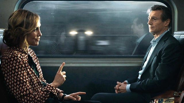 De två huvudrollerna i The Commuter sitter mittemot varandra på ett tåg.