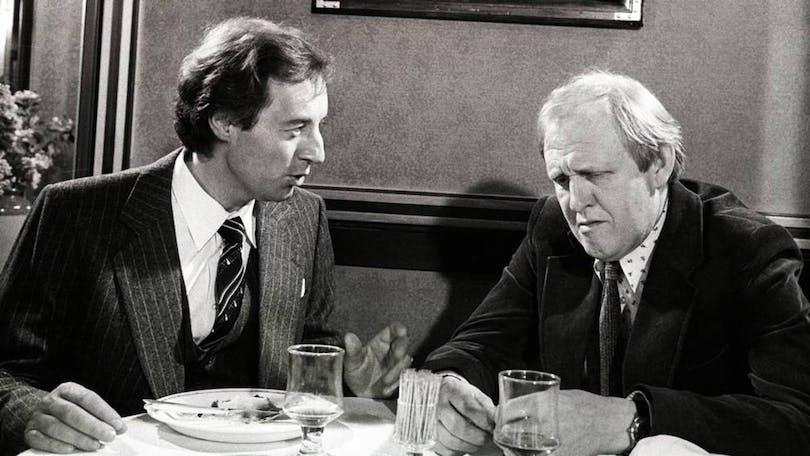Från kriminalserien Dubbelstötarna. Två män sitter och äter lunch tillsammans.