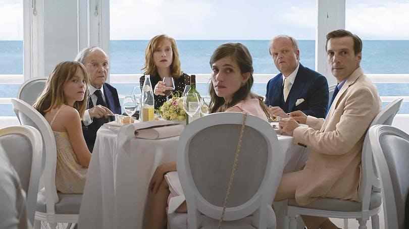 """Huvudrollerna i """"Happy End"""" sitter runt ett bord."""