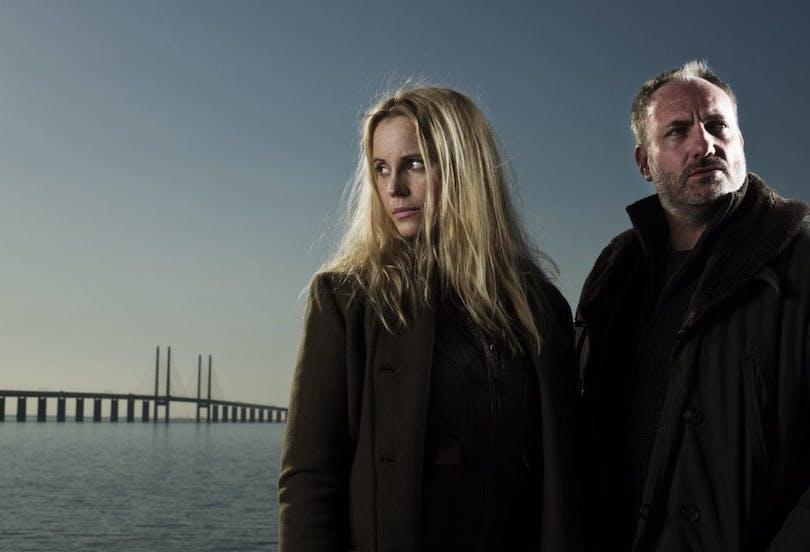 Från kriminalserien Bron. Två personer står till höger med Öresundsbron bakom sig.