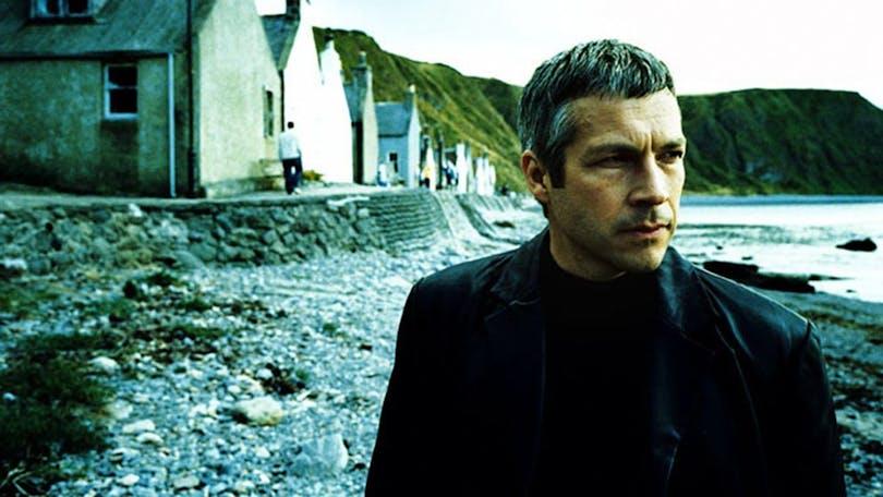 Från kriminalserien Kommisarie Winter. En man går på en stenstrand och tittar ut på havet.