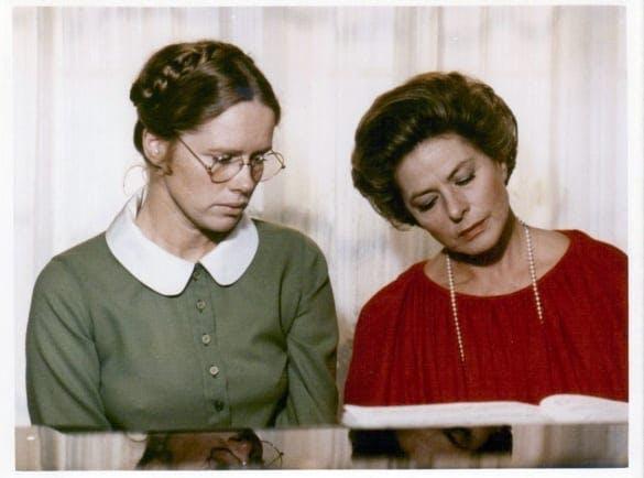Liv Ullmann och Ingrid Bergman sitter vid ett piano.