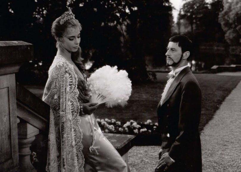 Ulla Jacobsson och Gunnar Björnstrand står mitt emot varandra i Sommarnattens Leende av Ingmar Bergman.
