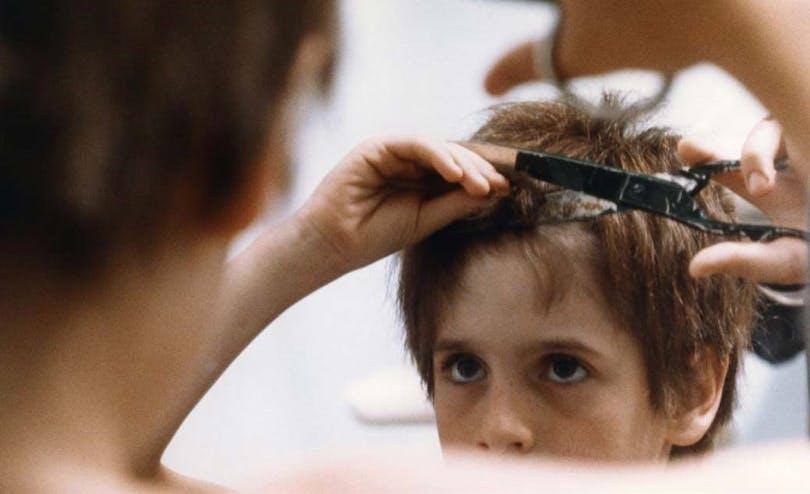 En pojke klipper sig i håret framför spegeln.