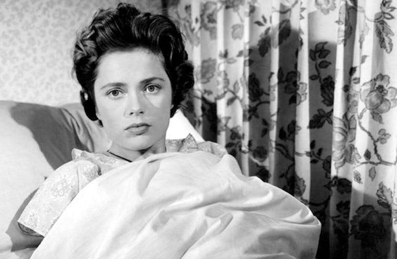 Ulla Jacobsson ligger i en säng och kollar in mot kameran.