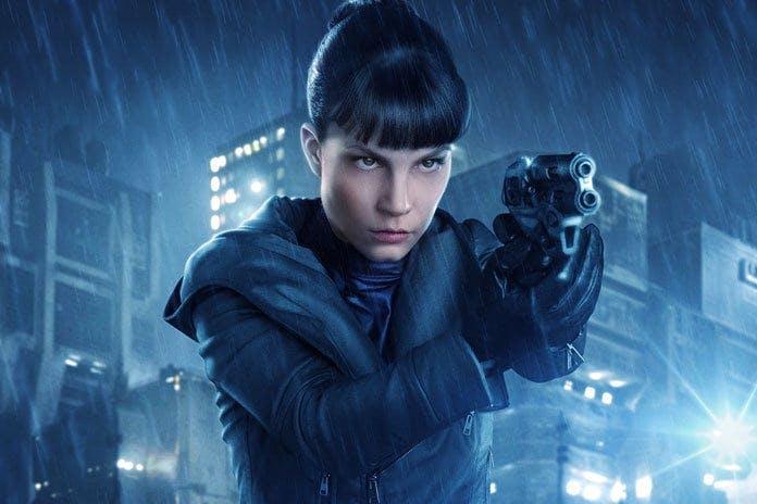 Här ser du en bild på karaktären Tara Chace som håller en pistol.