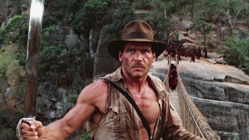 Indiana Jones står på hängbro.
