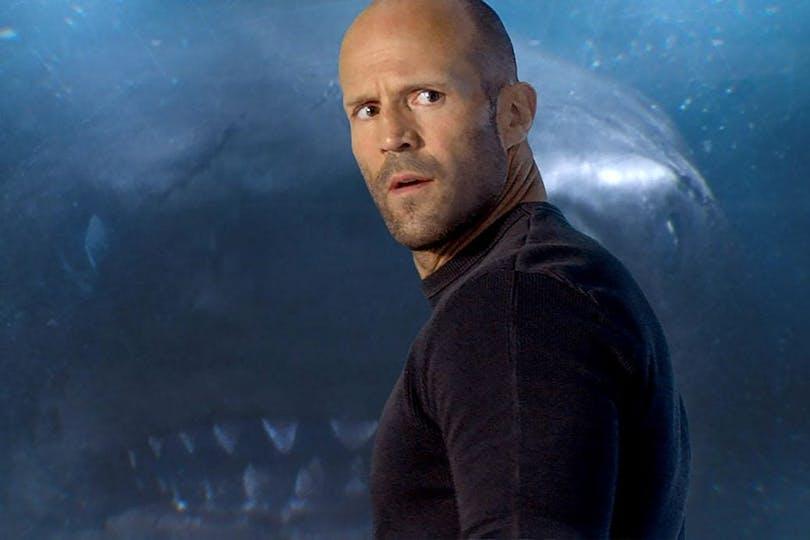 Jason Statham står framför en jättehaj.