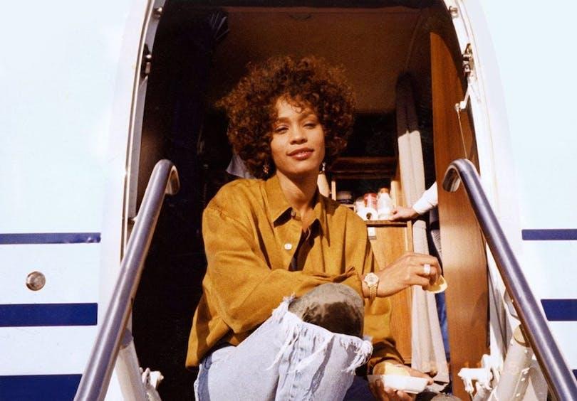 Whitney Houston framför ingången till ett flygplan.