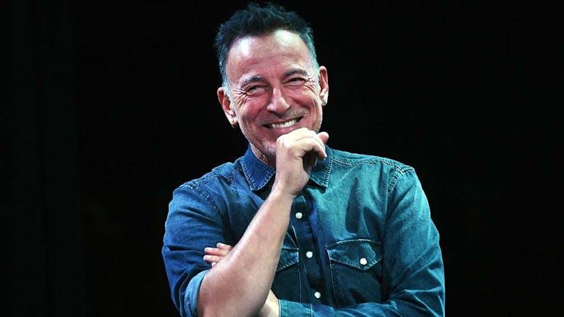 Bruce Springsteen håller i en mikrofon och ler.