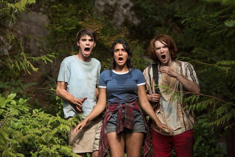 Tre av ungdomarna står i skogen och stirrar förfärat med öppna munnar.