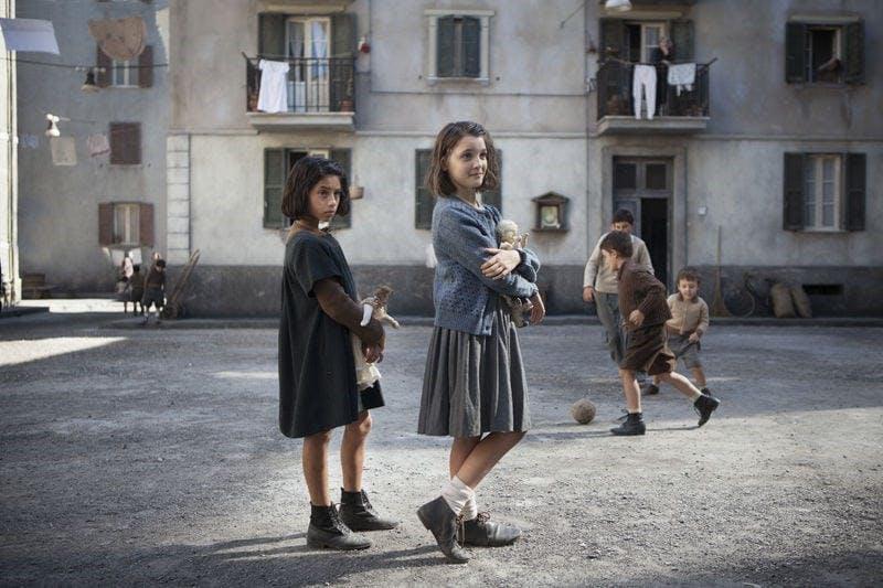 Två flickor står på en bakgård i Neapel.