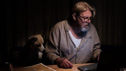 Rolf Lassgård och en hund betraktar en dator i ett mörkt rum