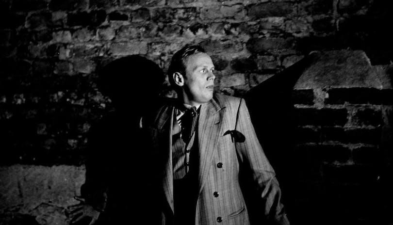 Richard Widmark står emot en tegelvägg.