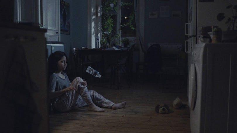 En sitter på golvet framför en tvättmaskin.