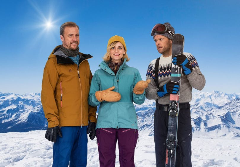 Huvudrollsinnehavarna i Carl-Johan, Frank och jag står med skidutrustning en solig dag.