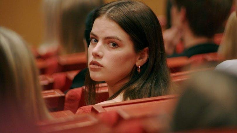Felicia (Alva Bratt) vänder sig om i sätet i föreläsningssalen.