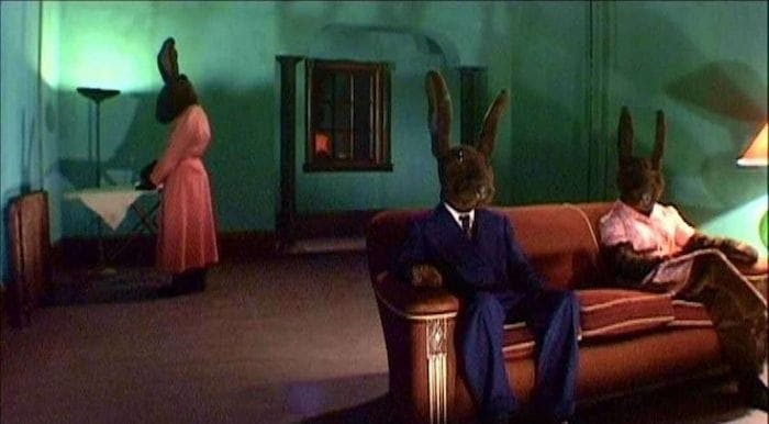 "Kaniner i kostym sitter i en soffa i David Lynchs ""Inland Empire""."