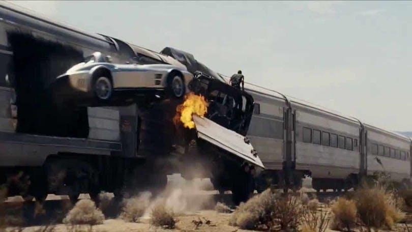 Ett ökenfordon sitter fast i ett tåg medan en bil hoppar från samma tåg i Fast Five.