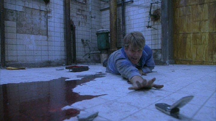 En av huvudkaraktärerna försöker nå en telefon i Saw